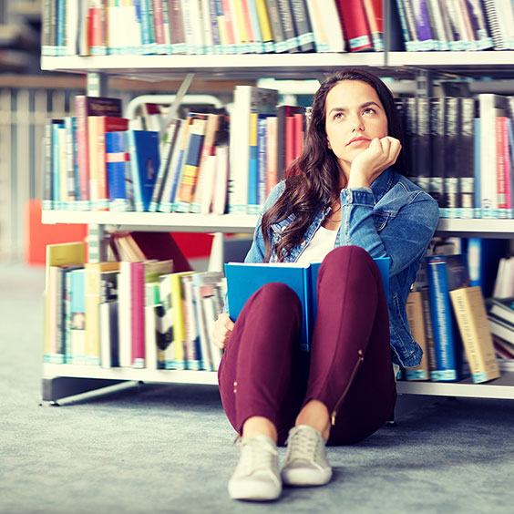 Student in thoughts in front of bookshelf